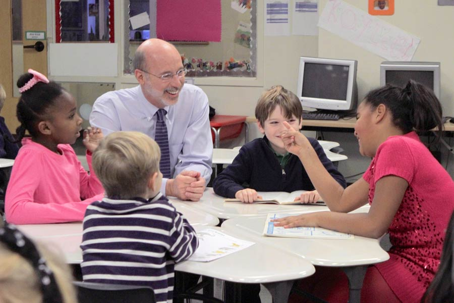 A photo of Tom Wolf with children at a school