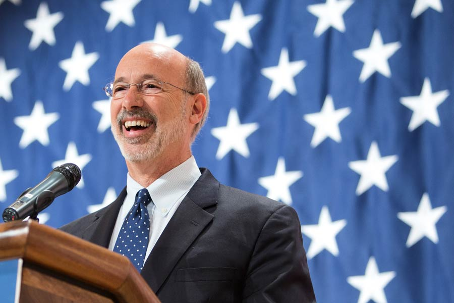 A photo of Tom Wolf in front of a large American flag